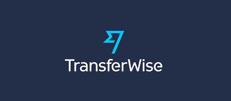 Logo TransferWise bandiera celeste con scritta bianca TransferWise sotto e sfondo blu scuro
